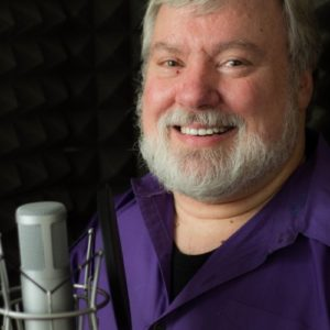 Headshot of Michael, smiling in front of a voiceover microphone.