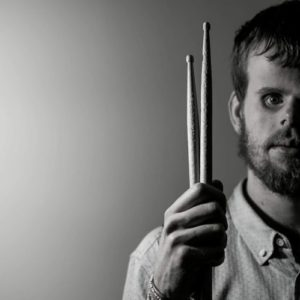 Headshot of Tommy Carroll, holding drumsticks